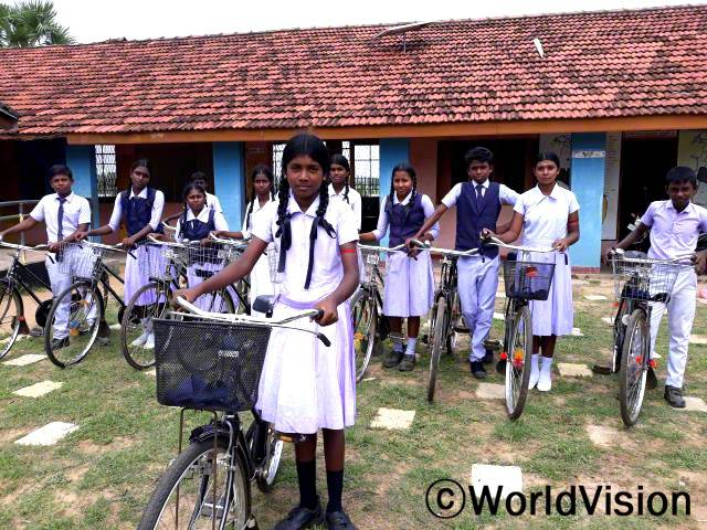 """""""전에는 학교에 가려면 몇 시간씩 걸어가야 했는데 후원자님 덕분에 자전거를 지원받아 안전하게 등교하며 더 이상 학교에 지각하지 않아요."""" -카잘라츠시(13세)년 사진"""