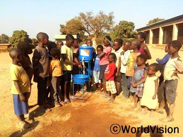 마을 아이들은 위생용품을 받아 학교 세면대에서 손을 깨끗이 씻고 있습니다.년 사진