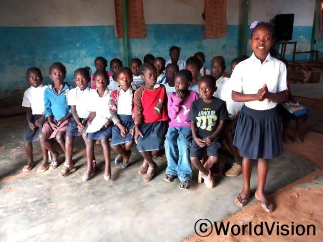 클레멘타인(10세, 일어서 있는 아동)은 마을에 있는 개인지도센터에서 읽기와 쓰기 실력을 키웠습니다.년 사진