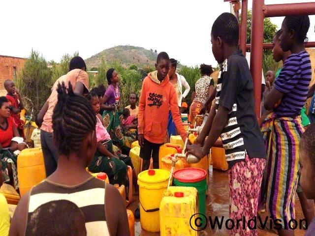 예전에는 깨끗하지 않은 우물에서 떠온 물을 마셔서 저희 마을 아이들이 수인성 질병에 걸렸어요. 이제는 저희 집 근처에 수도시설이 생겼고, 깨끗한 물을 마실 수 있어요. -세드릭(10세, 주황색 티셔츠)년 사진