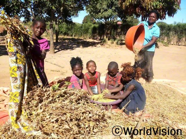 디바인은 동생들과 함께 부모님을 도와 수확한 콩의 껍질을 벗기고 있습니다. 그녀의 부모님은 월드비전의 도움으로 농업 교육을 지원받았습니다.년 사진
