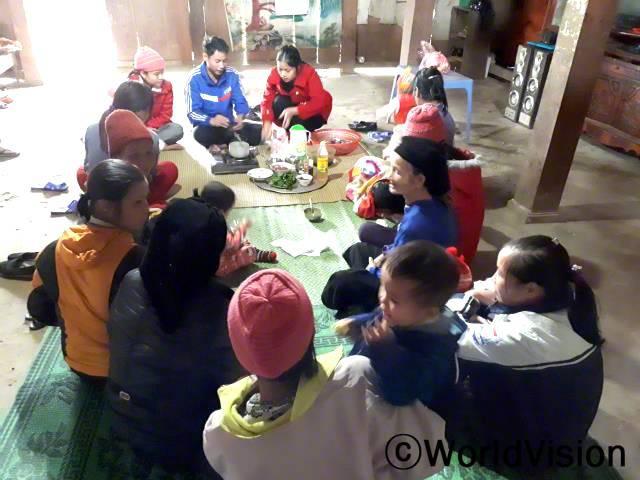 우리 마을의 영양 모임에 가입한 뒤, 저는 아이들을 위한 수프를 만들 때, 언제 야채를 넣어야 하는지 알게 되었어요. 그 결과, 제 아이들은 음식을 매우 잘 먹고 몸무게도 늘었어요. -호앙, 영양클럽 멤버 (빨간 옷을 입고 있는 사람)년 사진