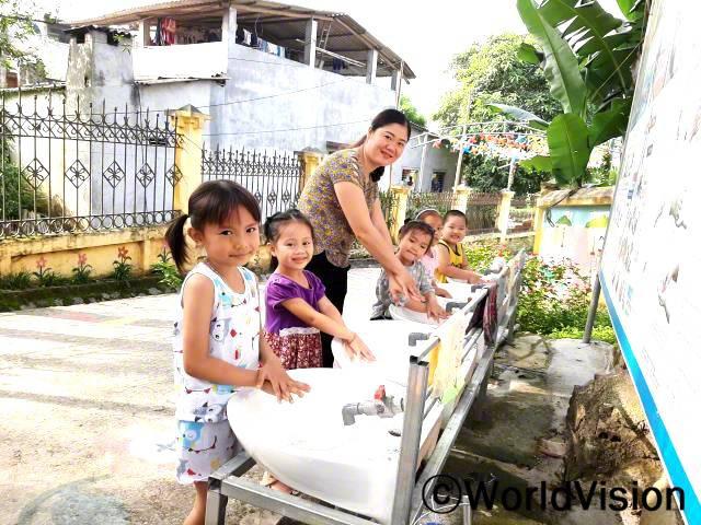 """""""월드비전 덕분에, 선생님들은 더 이상 물을 길러 멀리 갈 필요가 없습니다. 아이들은 세면대에서 깨끗한 물을 매일 사용하고 있습니다. 아이들은 식사 전후로 손을 씻는 방법을 배워서, 더 이상 설사나 눈병에 걸리지 않습니다."""" -본, 선생님년 사진"""