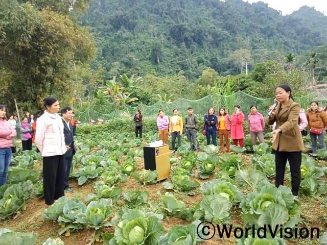 """""""마을의 대부분의 가정들은 생계를 위한 소득증대 모임에 참여하고 있습니다. 그들은 월드비전을 통해 채소를 기르고 재배하는 훈련을 받았어요. 그 결과, 그들의 수입은 더 안정적이게 되었고, 아이들에게 영양가 있는 음식을 만들어줄 수 있게 되었습니다."""" -카우, 소득증대모임 회장, 마이크를 들고 있는 여성년 사진"""