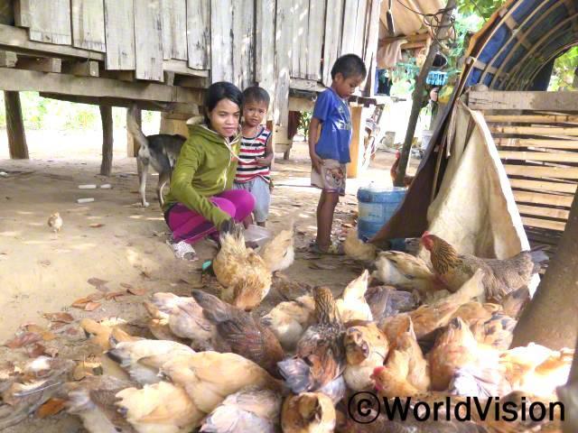 저희 아이들은 영양실조 상태였어요. 이제는 닭들이 건강하여, 아이들에게 달걀과 닭고기를 먹일 수 있게 되었어요. 남는 것은 시장에 내다 팔아 아이들의 학교 경비를 충당할 수 있게 되었고, 더 많은 닭을 키울 수 있게 되었어요. -푸옹, 엄마(스웨터를 입고 있는)년 사진