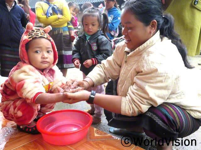 더러운 손으로 음식을 먹으면 아이들이 병에 걸린다는 걸 배웠어요. 밥 먹기 전에는 늘 잊지 않고 아이들이 손을 씻을 수 있게 돕는답니다.- 뚜 (영양 결핍이었던 아동의 보호자, 노란 코트를 입은 사람)년 사진